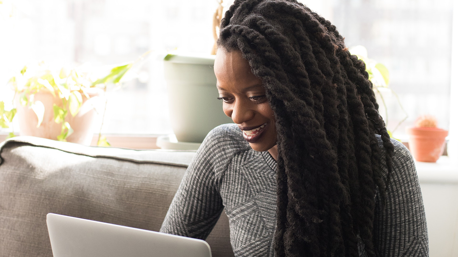 Woman on laptop at home smiling