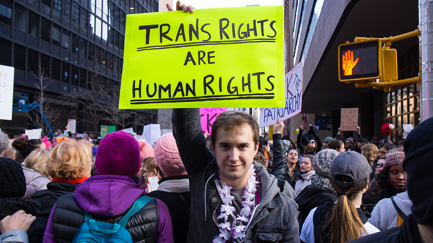 "Student holding a sign that reads ""Trans Rights are Human Rights"""