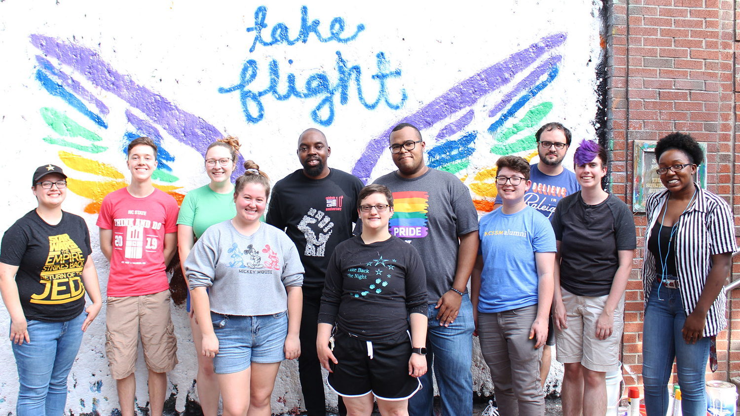 Students in front a mural that says Take Flight