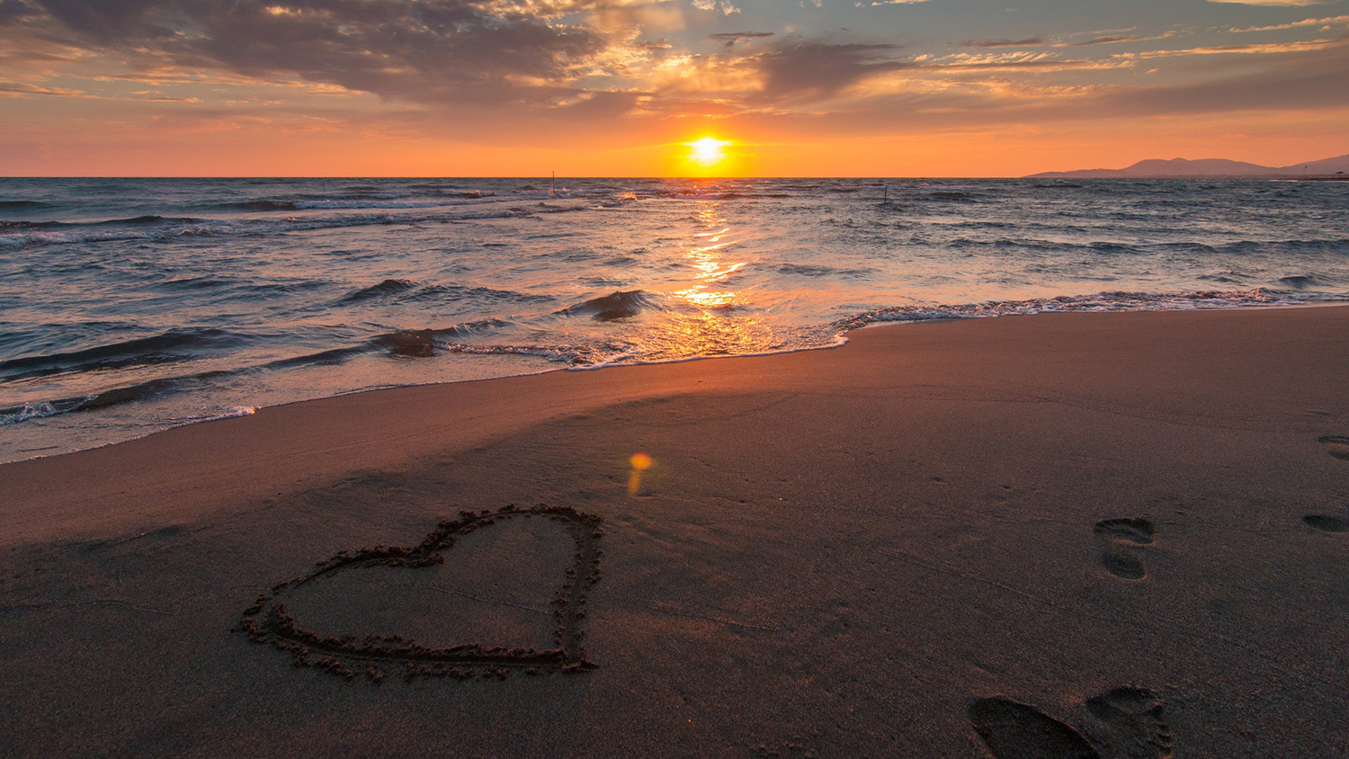Beach sunset with heart drawn in the sand