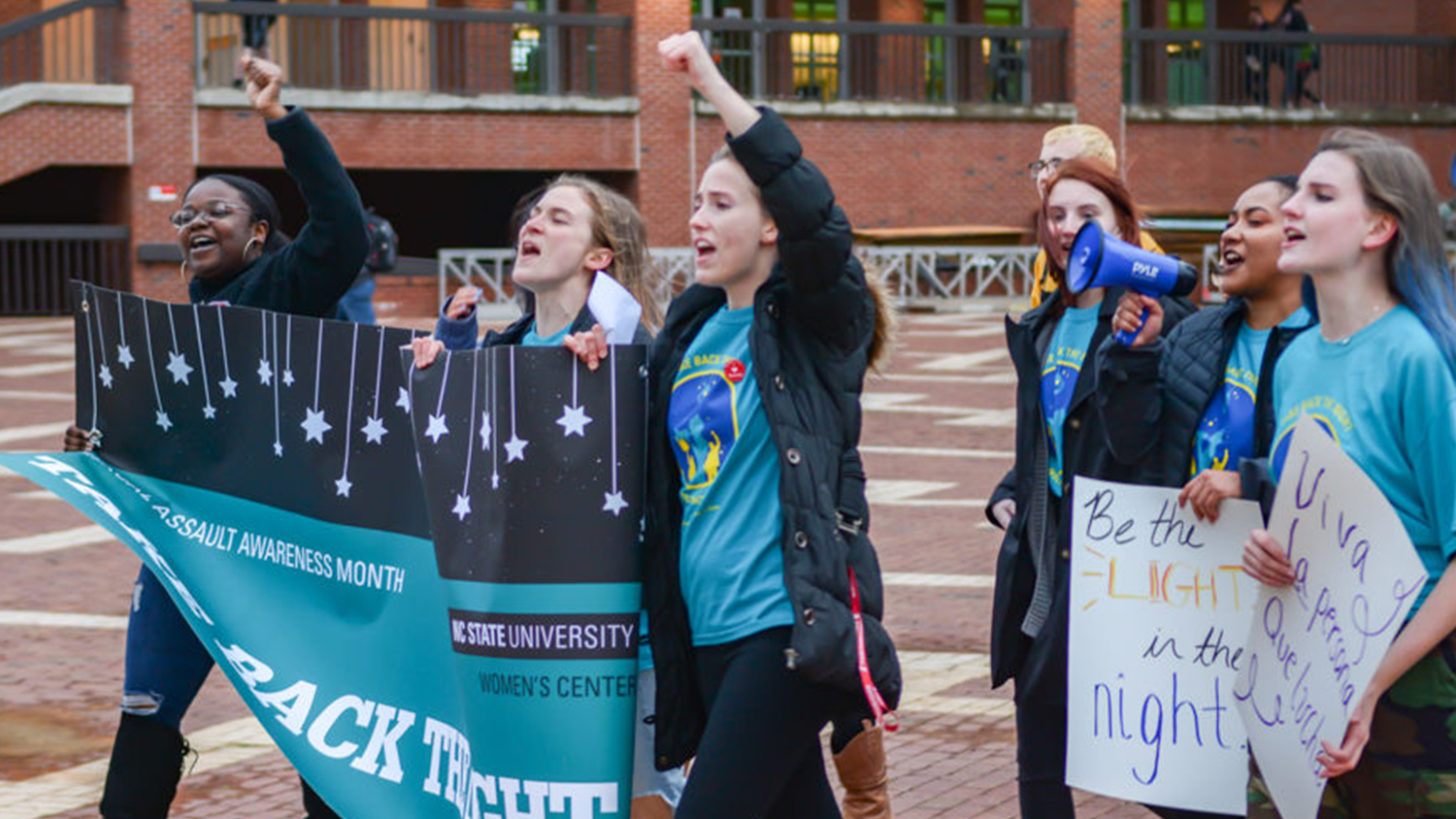 Students marching across the Brickyard at Take Back the Night