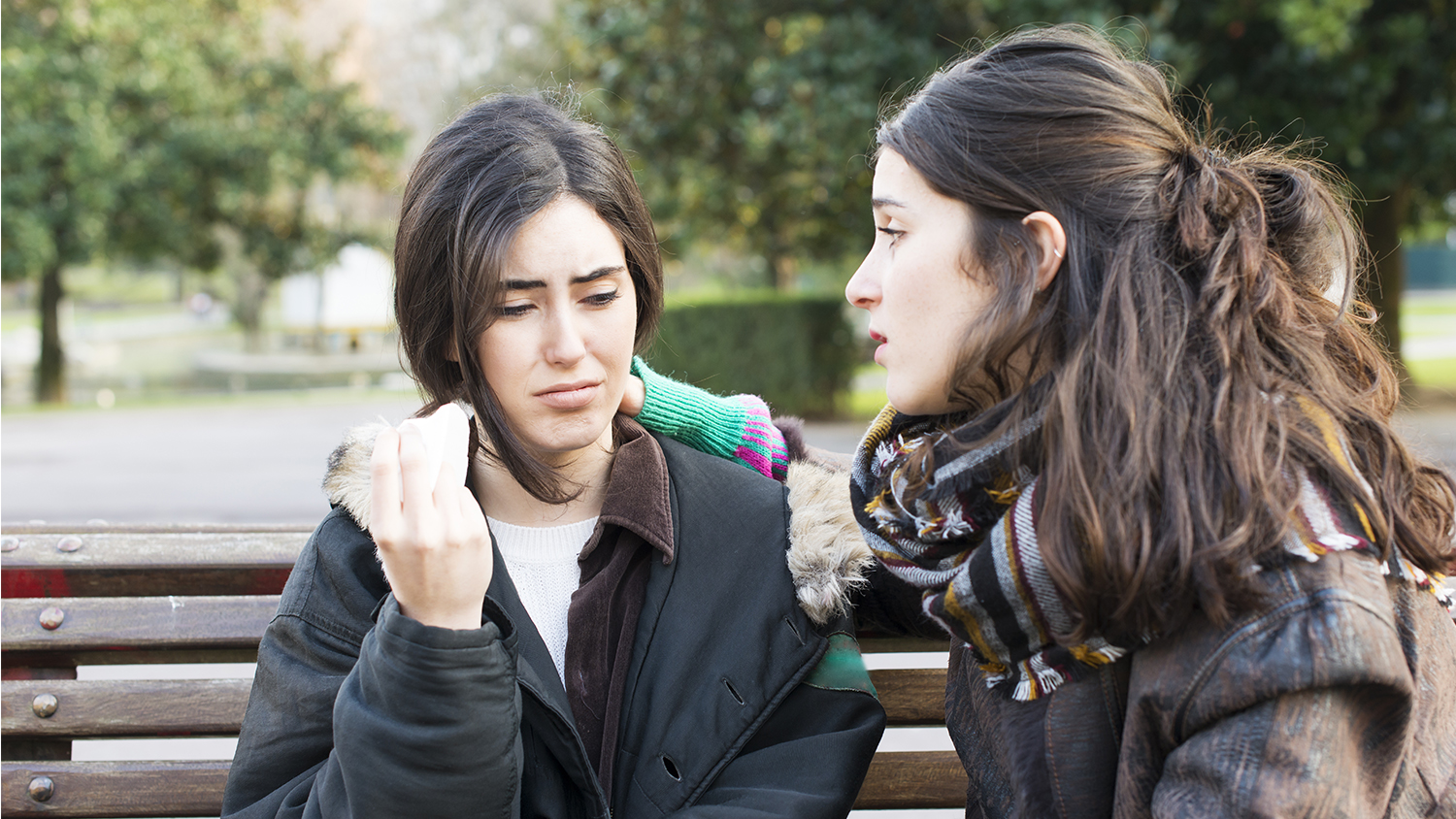 Two young women in discussion on a bench