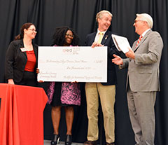 Chancellor Woodson congratulates 2015 Chancellor's Creating Community award recipient, the College of Humanities and Social Sciences