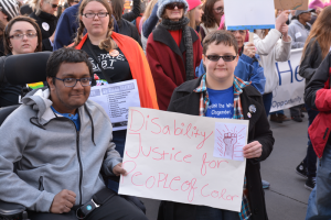 Students holding up a Disability Justice for People of Color sign