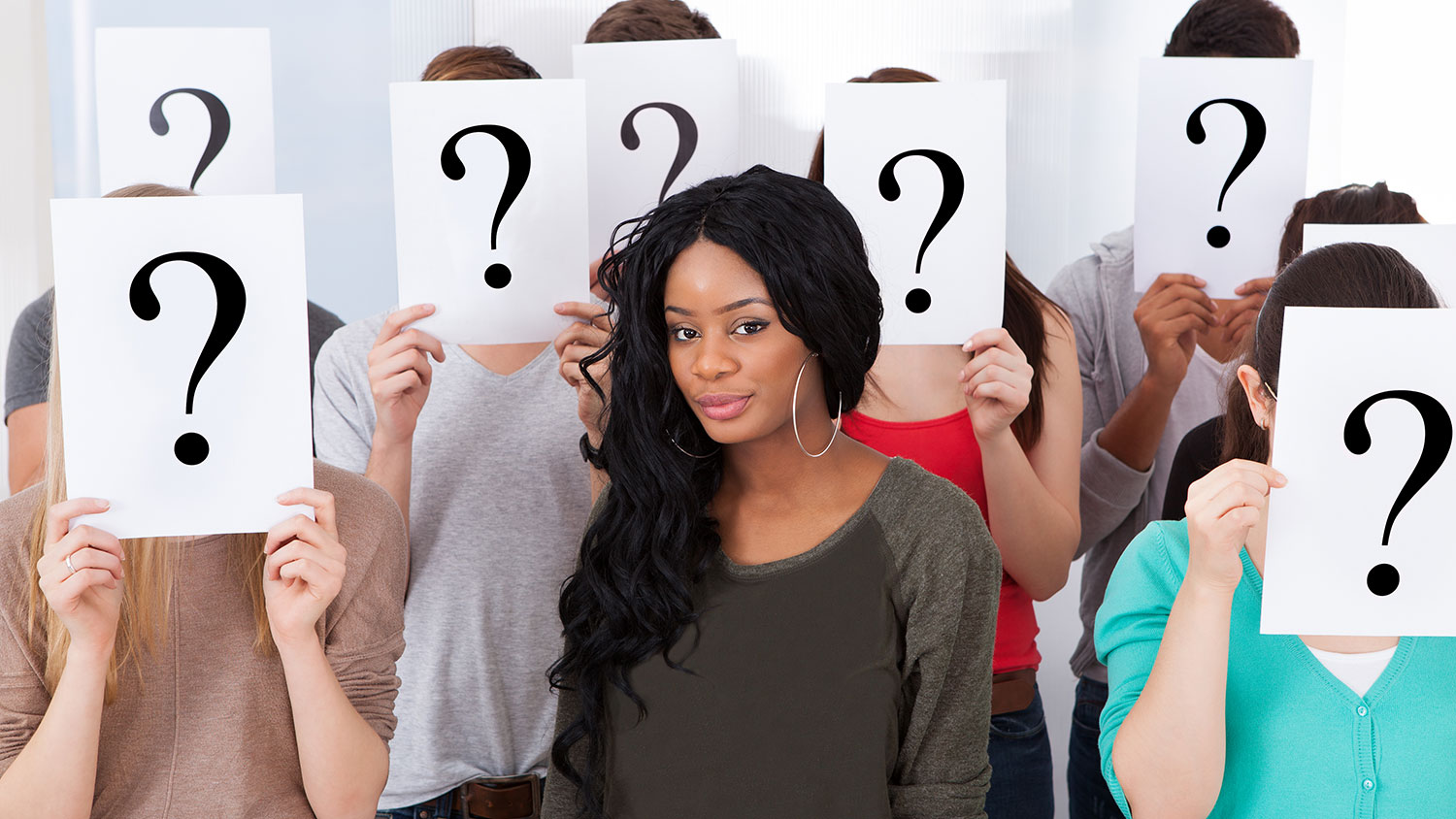 Young Black woman surrounded by White people with question mark signs over their faces