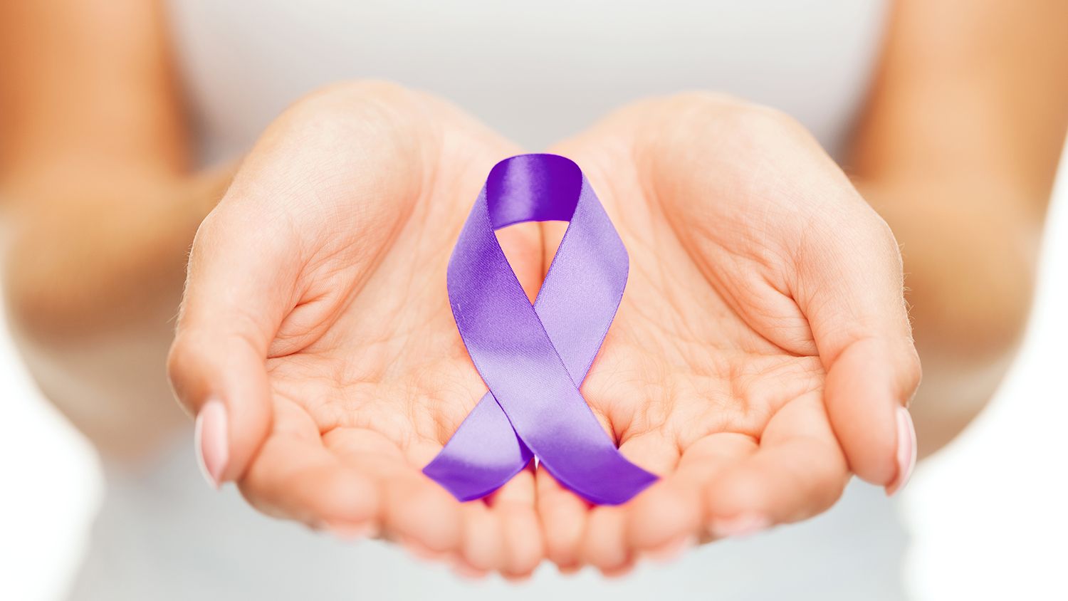 Hands holding purple ribbon