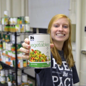Women holding up can of food and smiling at food pantry
