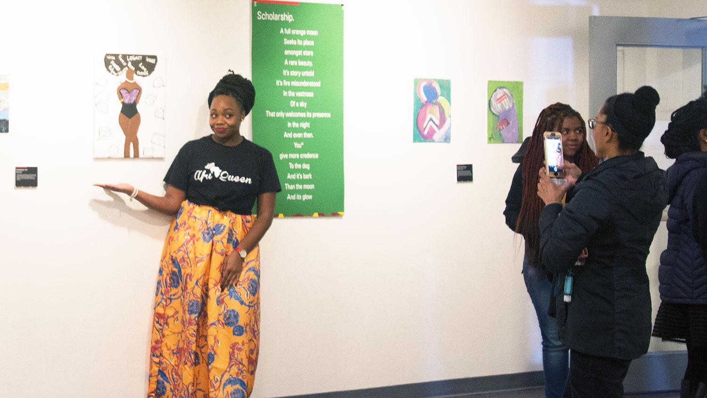 Black Bodies Exhibit artist poses with artwork