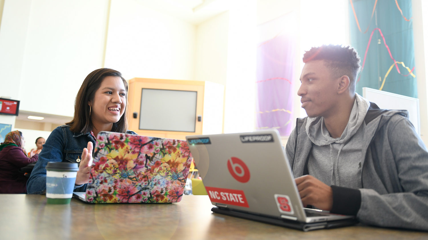 Diverse students studying at laptops