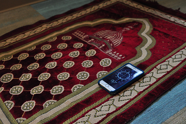 Prayer rug and compass in prayer space
