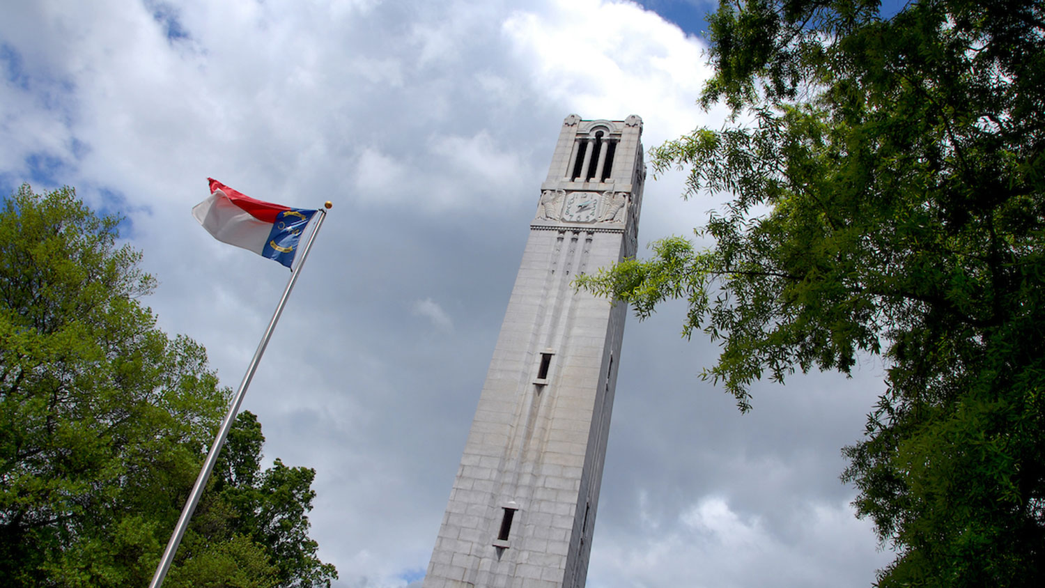NC State Belltower on a cloudy day with state flag