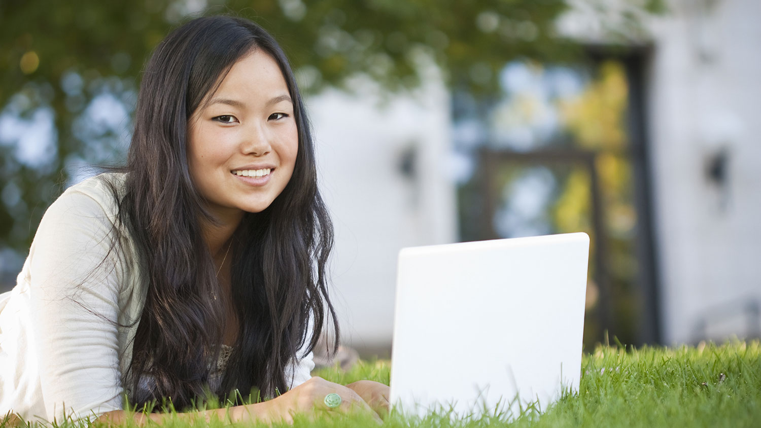 Smiling girl outside with laptop