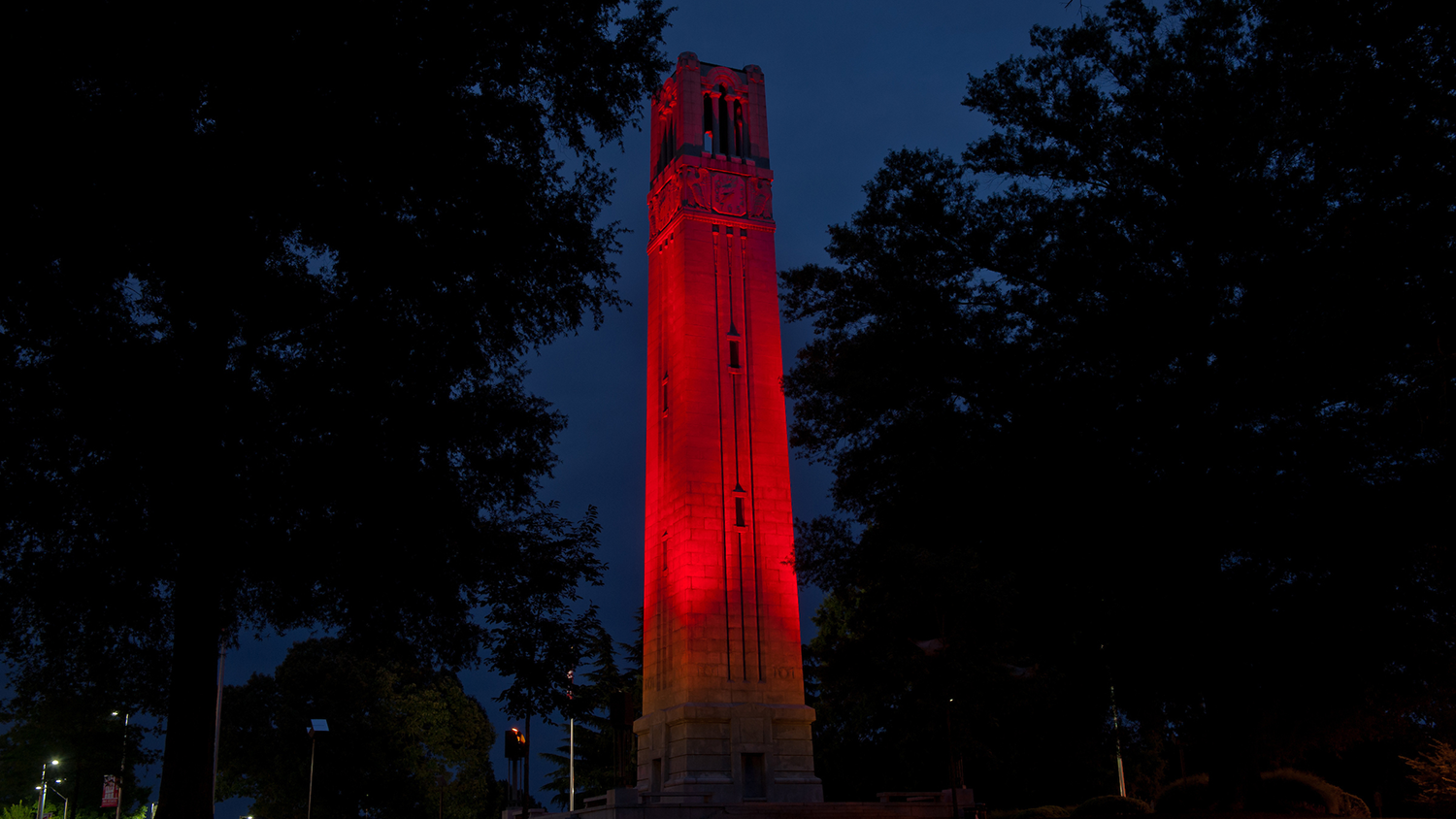 NC State Belltower lit up red at night