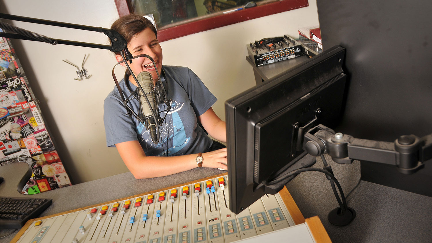 Student in front of a microphone recording.