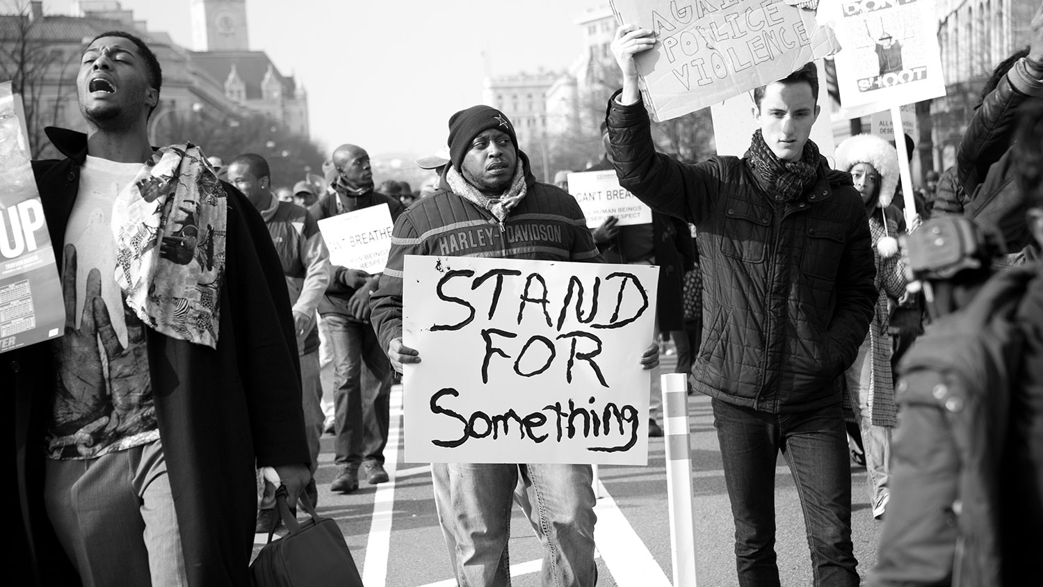 "Protestor with ""Stand for something"" poster"