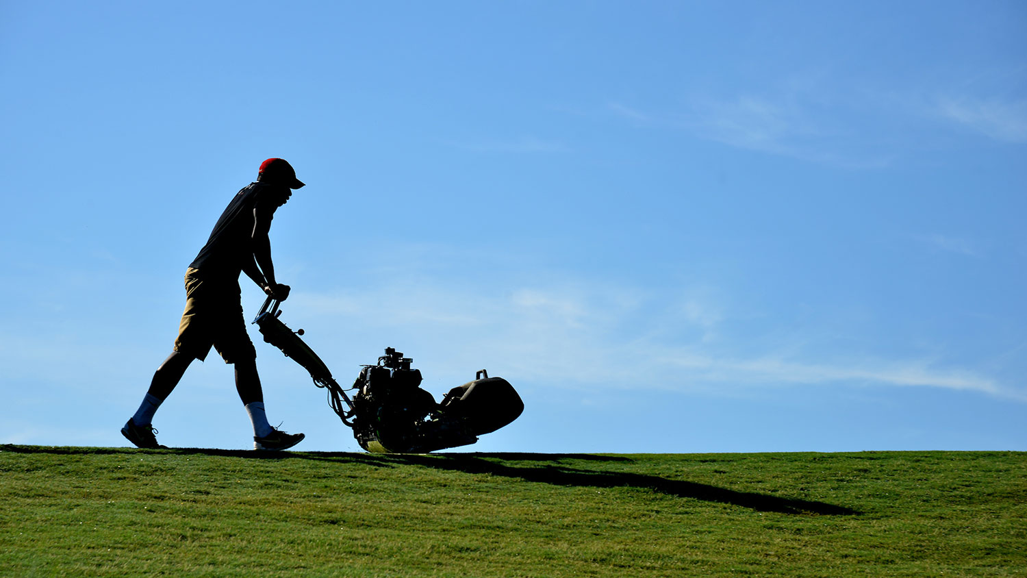 A man mows the golf course