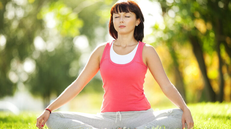 Woman in lotus yoga pose with eyes closed in a sunny meadow