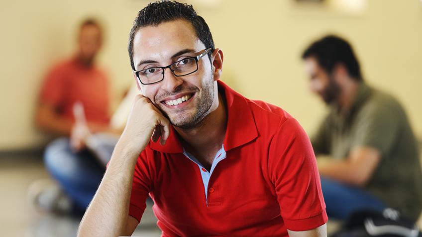 Male Student in a red polo style shirt with his head on his hand smiling at the camera